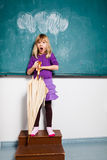 Surprised young girl with umbrella indoors Stock Images