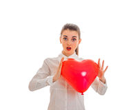 Surprised young girl in white shirt holding a large inflatable balloon sweetheart Royalty Free Stock Image