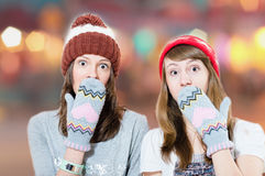 Surprised young girls in hats and mittens Stock Photos