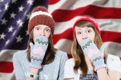 Surprised young girls in hats and mittens Stock Image