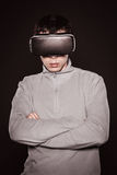 Surprised young in the gray sweater, the man in the glasses of virtual reality. Stock Photo
