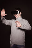 Surprised young in the gray sweater, the man in the glasses of virtual reality. Royalty Free Stock Photo