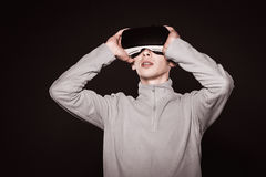 Surprised young in the gray sweater, the man in the glasses of virtual reality. Stock Photos