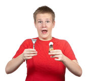 The surprised young guy in a red t-shirt with the razor and a small brush in hands Stock Photos