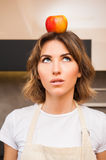 Surprised young lady with an apple on her head Stock Image