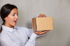 Surprised young lady opening a package Royalty Free Stock Photography