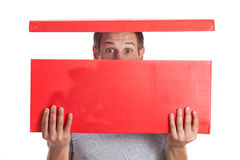 Surprised young man. Surprised man with head in red box Stock Image