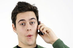 Surprised young man on cell phone Royalty Free Stock Image