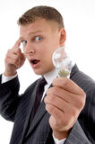 Surprised young man holding electric bulb, Royalty Free Stock Photography