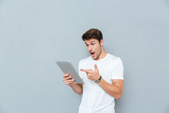 Surprised young man holding and pointing on tablet. Over grey background Royalty Free Stock Photography