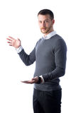 Surprised young man holding smartphone and something Royalty Free Stock Photos