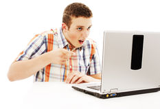 Surprised young man with laptop. Pointing at it. Stock Photos