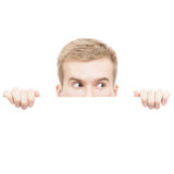 Surprised young man  looking from behind a board isolated on white background Royalty Free Stock Images
