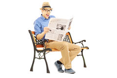 Surprised young man reading the news seated on a bench Stock Images