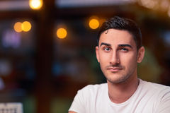 Surprised Young Man Sitting in a Restaurant Royalty Free Stock Image