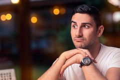 Surprised Young Man Sitting in a Restaurant Royalty Free Stock Photos