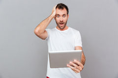 Surprised young man in white tshirt holding tablet Royalty Free Stock Photo