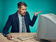 Surprised Young Man Working On computer At Desk Royalty Free Stock Photos