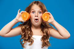 Surprised young pretty girl holding oranges over blue background. Stock Photo