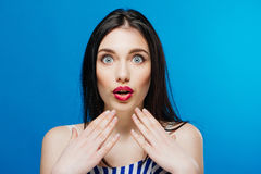 Surprised young pretty girl looking at the camera isolated on the blue background Stock Photography