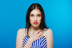 Surprised young pretty girl looking at the camera isolated on the blue background Royalty Free Stock Photos
