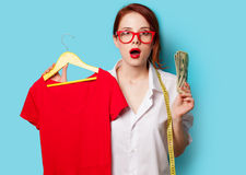 Surprised young redhead designer with dress and dollars Royalty Free Stock Photos