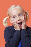 Surprised young schoolgirl with hands on face over orange background Stock Image
