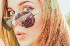 Surprised Young Woman in Sunglasses. Closeup of surprised young woman in aviator sunglasses outdoors in the sun Stock Photo