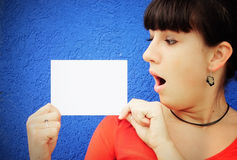 Surprised young woman. Image of a surprised young woman reading a note Royalty Free Stock Images
