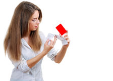 Surprised young woman. Stock image of surprised young woman looking at sale ticket after shopping too much and overspending holding credit card in another hand Royalty Free Stock Photos
