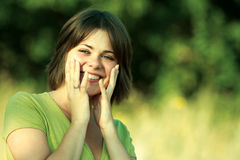 Surprised young woman. Smiling young woman holds her face in surprise Royalty Free Stock Photography