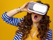 Surprised young woman against yellow background using VR gear Stock Photos