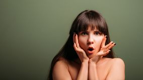 Surprised amused shocked emotion woman portrait. Surprised young woman. Amused facial expression. Closeup portrait of emotional brunette lady with hands at her stock images