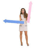 Surprised young woman with arrows pointing Royalty Free Stock Photography