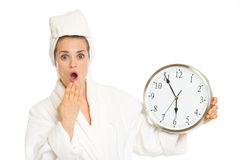 Surprised young woman in bathrobe with clock. Isolated on white stock image