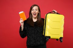 Surprised young woman in black fur sweater with opened mouth holding suitcase, passport boarding pass ticket isolated on stock images