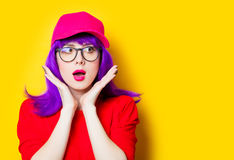 Surprised young woman in cap and glasses. Portrait of beautiful surprised young woman in cap and glasses on the wonderful yellow studio background Royalty Free Stock Photography