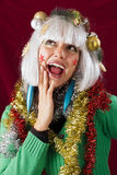 Surprised young woman at Christmas. Christmas decorated woman with open mouth looking surprised. Studio shot against a red background Royalty Free Stock Images