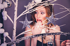 Surprised young woman among Christmas decoration Royalty Free Stock Images