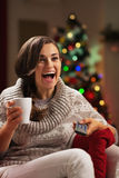 Surprised young woman with cup of hot chocolate watching tv Royalty Free Stock Images