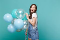 Surprised young woman in denim clothes keeping mouth wide open, celebrating, holding colorful air balloons isolated on royalty free stock photo