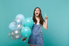 Surprised young woman in denim clothes looking, pointing index finger up, celebrating hold colorful air balloons