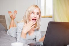 Pretty woman using laptop while having a cup of coffee on bed royalty free stock photo