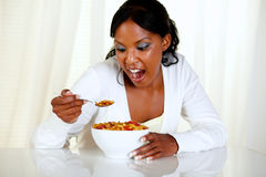 Surprised young woman eating a bowl of cereals Royalty Free Stock Photography