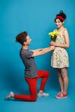 Surprised young woman getting flower from guy Stock Images