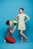 Surprised young woman getting flower from guy Royalty Free Stock Images