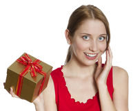 Surprised Young Woman with Gift Box. Young woman in a bright red dress, holding a golden gift box with a surprised delighted Stock Photography