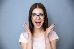 Surprised young woman in glasses. Over gray background Royalty Free Stock Photography