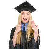 Surprised young woman in graduation gown Stock Images
