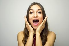 Surprised young woman with hands near open mouth looking at camera on gray background.  Royalty Free Stock Photos